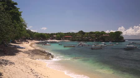 Beautiful tourist Mushroom beach on Nusa Lembongan island. Many boats, yachts and jet skis swing on the waves of azure Indian Ocean near the coastline at bright sunny day. 50 fps full hd footage. Wideo