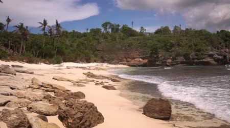 Beautiful deserted beach without people in secret lagoon surrounded by cliffs on Nusa Ceningan island. Frothy waves of azure Indian Ocean wash sand limestone rocks surrounded by palm trees and bushes.
