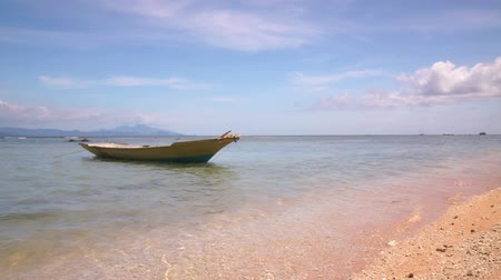 Small wooden boat bobs and swings on calm waves on leash at picturesque deserted beach without people. Calm sea waves of the turquoise Indian Ocean washes the sandy shore. 50 frames per second Full HD