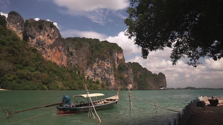 cauda : Traditional long-tailed Asian boat bobs on calm waves of Andaman Bay near Railay Beach, Krabi. Large rocky cliff with green vegetation and blue sky in background. 50 frames per second full hd footage.