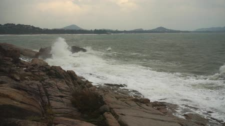 rohanó : Large storm waves crashing on rocks in slow motion. Foamy waves hit the volcanic stones of the Andaman Sea shore at stormy cloudy weather. Tropical Island of Koh Samui, Thailand. Stock mozgókép