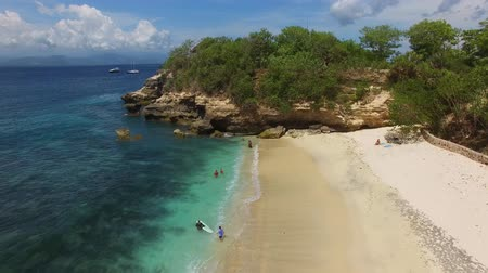 águas : Flying over deserted Mushroom beach to a small cliff with green vegetation on top. Turquoise waters and waves of Indian Ocean wash sandy shore on bright sunny day. Aerial of Nusa Lembongan, Bali.