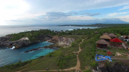 gruta : Rising above rocky ledges with green vegetation, village houses, hiking paths on top. Grottoes and lagoons washed by waters of turquoise ocean. Foamy waves break on stones. Aerial of Nusa Ceningan. Stock Footage