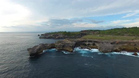 gruta : Rocky ledges with green vegetation, village houses, hiking paths on top. Volcanic grottoes and lagoons washed by waters of turquoise ocean. Foamy waves break on stones. Aerial of Nusa Ceningan. Stock Footage