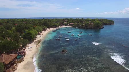 bobbing : Flying high above Mushroom Beach with yellow sand, lush vegetation, luxury villas, resorts and variety of boats and yachts bobbing on foamy waves of turquoise Ocean. Aerial of Nusa Lambongan, Bali.