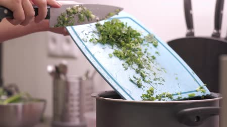 field kitchen : Young woman housewife drops greens, onions, dill and parsley to the pot. Preparing food ingredients on a stone countertop in a home kitchen. 4k 50 frames per second narrow depth of field.
