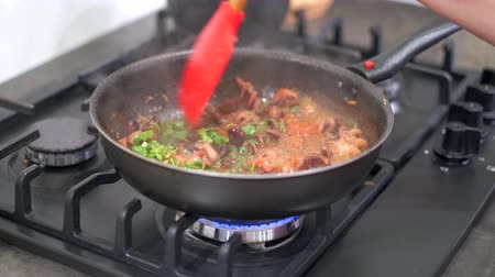 polip : Chef stir fried vegetables and baby octopus in a hot frying pan. Cooking seafood at home on a modern gas stove. 4k 50 frames per second narrow depth of field close up footage