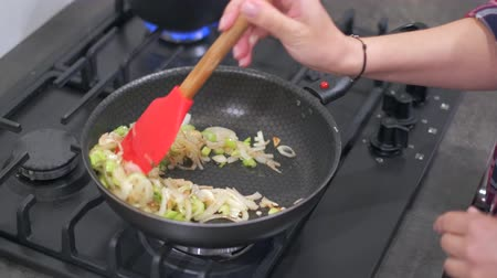 polip : Young woman housewife stirring fried onions and green pepper in a hot frying pan. Cooking at home on a modern gas stove. 4k 50 frames per second narrow depth of field close up footage Stock mozgókép