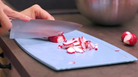 rabanete : Young woman housewife cuts radish on a blue plastic cutting board. Preparing food ingredients on a stone countertop at a home kitchen. 4k 50 frames per second narrow depth of field close up footage. Stock Footage