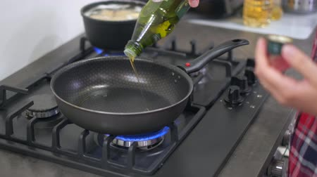 field kitchen : Young woman housewife heats the pan up and pours oil. Cooking food at home on a modern gas stove. 4k 50 frames per second narrow depth of field close up footage. Stock Footage