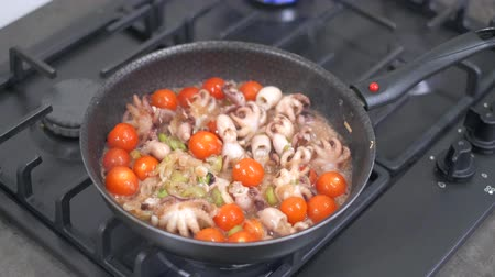 polip : Stir fried baby octopus and vegetables in a hot frying pan. Cooking seafood dish at home on a modern gas stove. 4k 50 frames per second narrow depth of field. Close up footage.