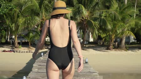 takip etmek : Young caucasian woman in sunglasses swimsuit and straw hat happily walks on wooden jetty pier towards the beach on tropical island and invites to follow her with a hand. Slow motion follow me footage Stok Video