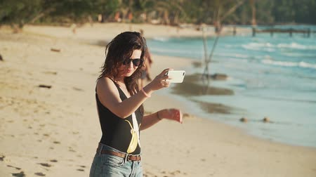 fotoğraflar : Pretty young woman in sunglasses and swimsuit takes selfie on beautiful sandy beach by sea. Happy smiling girl pulls her hair, spinning and taking pictures of herself with smartphone. Slow motion.