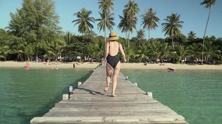 wooden bridge : Young caucasian woman in swimsuit and straw hat happily runs along wooden jetty pier to tropical island coast sandy beach and green palm trees, bushes and foliage on bright sunny day. Slow motion.