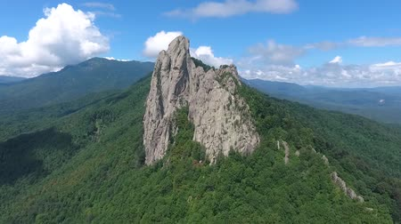 outlier : A large rock outcrops against the blue cloudy sky. Aerial view. Stock Footage