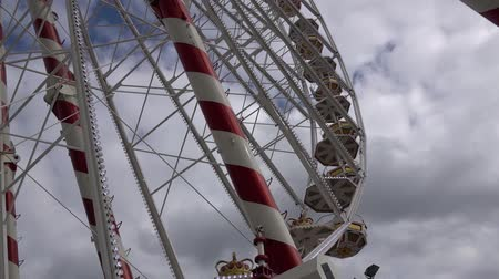 donuk : An empty Ferris wheel spins against a dramatic cloudy sky.