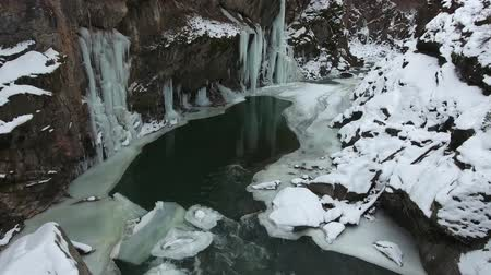 절벽 : Winter mountain landscape. Rapids on the fast river in the gorge with icicles on the walls of the cliff.