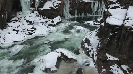 rampouch : Flight over the winter river at the bottom of the gorge. Icicles hang from the stone walls of the gorge.