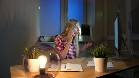 verificador : Shocked female at computer talking on smartphone. Sitting in dark room at wooden desk with notebook young blond woman talking on mobile phone and looking stunned at computer monitor. Stock Footage