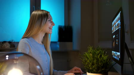 descontraído : Woman looking attentively at computer at night. Relaxed beautiful blond female in warm home clothing sitting at wooden table lit by small sphere lamp and concentrating on browsing on computer.