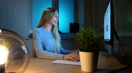 eleven : Smiling woman working on computer at night. Smiling female in checkered shirt sitting at lit by small lamp wooden desk and looking excitedly at computer monitor writing down information.