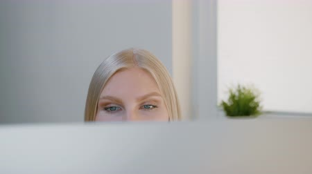 účetní : Female looking at computer monitor. Blond attractive woman sitting at window and looking attentively at computer screen shot made over top of monitor.