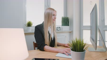 eleven : Smiling woman working on computer in office. Beautiful young blond female sitting at workplace with computer and holding hand on mouse looking at camera and smiling.