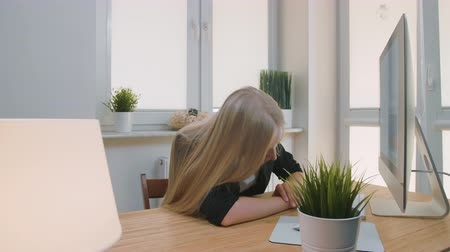 ukłon : Tired woman waking up at workplace. Tired blond female office worker in elegant suit relaxing lying on arms on desk then getting up yawning and starting working on computer in light room with plants.
