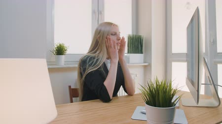 мигрень : Upset woman sitting at workplace. Blond sad female in elegant clothes clutching head after failure or bad news sitting in light office at desk with computer. Стоковые видеозаписи