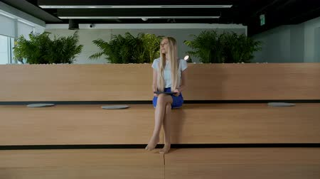 área de trabalho : Relaxing woman with tablet in office. Young elegant woman sitting barefoot on wooden tribune in modern office using tablet and taking rest.