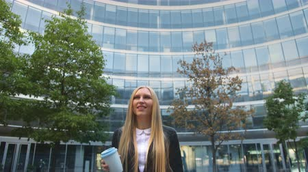 poháry : Stylish business woman with coffee on street. From below of serious blond executive woman in suit having coffee in paper cup looking away on street. Dostupné videozáznamy