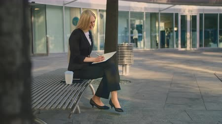 dinlenmek : Successful business woman taking notes outdoors. Side view of elegant businesswoman sitting on bench in patio and writing in notepad while working.