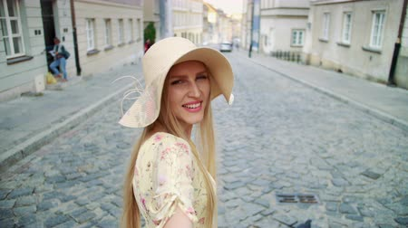 blondýnka : Woman gesturing follow me on street. Smiling young woman looking at camera and gesturing follow me on street.