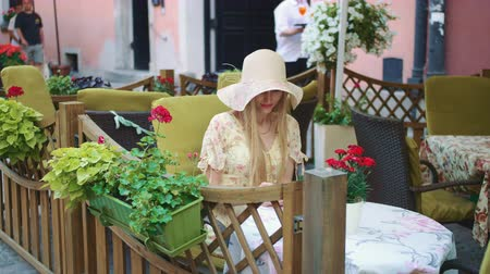 blondynka : Woman browsing smartphone in outside cafe. Cheerful woman sitting at table in outside restaurant and browsing smartphone. Wideo