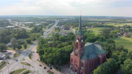 ethnographic : Church in small city among pastures. Red Church is Roman Catholic church. Stock Footage