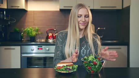 путаница : Young lady preferring hamburger to salad. Attractive young woman choosing to eat healthy hamburger for breakfast while sitting at table in stylish kitchen.
