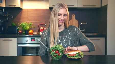 előny : Girl preferring salad to hamburger. Attractive young woman choosing to eat healthy salad for dinner while sitting at table in stylish kitchen. Stock mozgókép