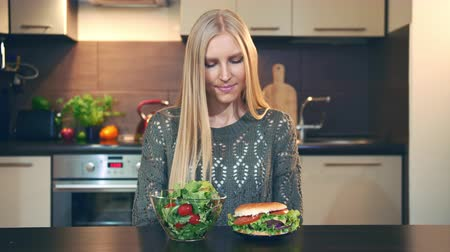 előny : Young woman preferring hamburger to salad. Attractive young woman choosing to eat healthy hamburger for supper while sitting at table in stylish kitchen and doing thumbs up gesture and looking at camera Stock mozgókép