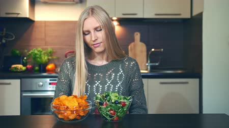 doubt : Young lady preferring crisp to salad. Attractive young woman choosing to eat healthy crisp for dinner while sitting at table in stylish kitchen.