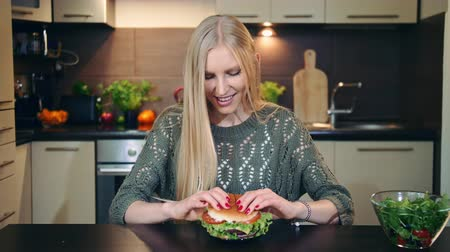 előny : Young woman eating fast food, hamburger while sitting at table in stylish kitchen.