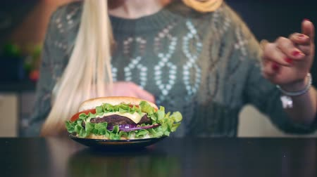 előny : Young lady preferring hamburger to salad. Attractive young woman choosing to eat healthy hamburger for breakfast while sitting at table in stylish kitchen.