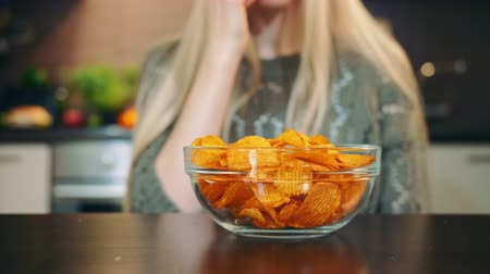 jíst : Glad woman eating potato chips. Beautiful young female enjoying potato chips and looking at camera while sitting in stylish kitchen.