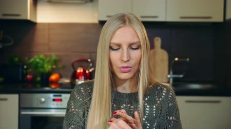 szőke : Young vlogger talking about makeup blush for face . Attractive young woman talking about cosmetic blush for face while shooting video for beauty vlog in kitchen.