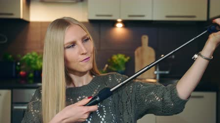 aplikatör : Young vlogger talking about selfie stick. Attractive young woman talking about selfie stick while shooting video for beauty vlog in kitchen.