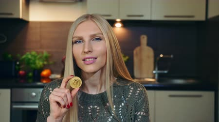 aplikatör : Young vlogger talking about bitcoin. Attractive young woman talking about bitcoin while shooting video for vlog in kitchen.