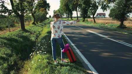 országúti : Young woman hitchhiking on countryside road. Stock mozgókép