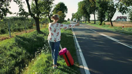 országúti : Anonymous Young lady hitchhiking on countryside road.