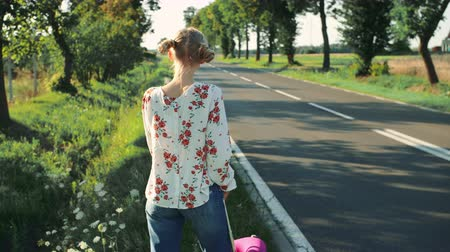 országúti : Young beautiful woman hitchhiking standing on the road with a suitcase. Stock mozgókép