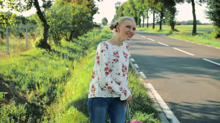 országúti : Traveler Young woman hitchhiking on countryside road.