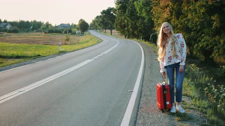 yol kenarı : Young lady hitchhiking on countryside road. Stok Video